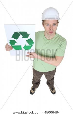 A construction worker holding a recycle sign.