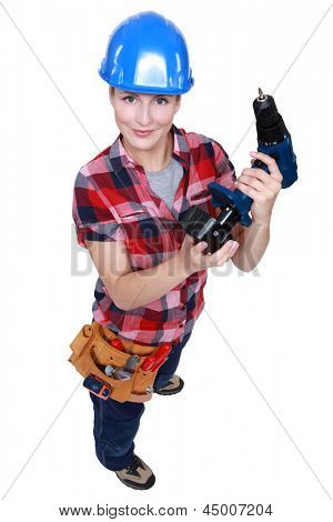 craftswoman putting the charger to a cordless drill
