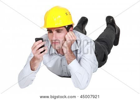 architect lying on floor looking annoyed at sms