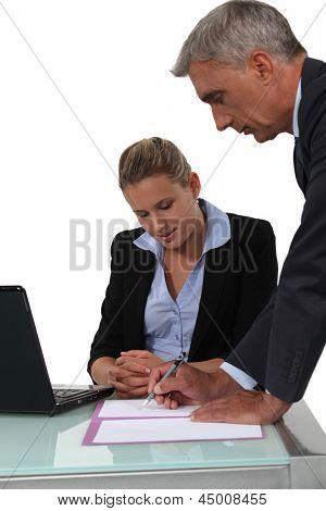 Secretary helping her boss fill in paperwork