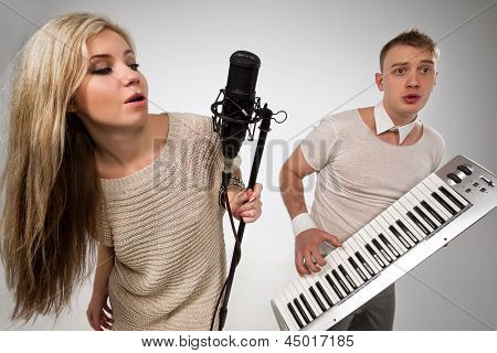 Couple performs duet singing microphone and playing on synthesizer