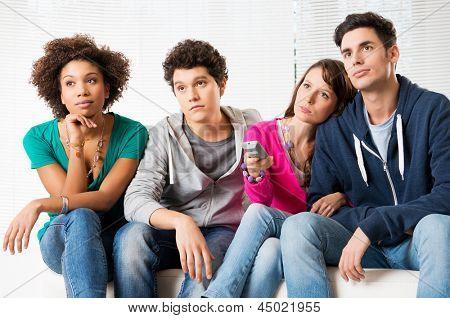 Group Of Young Friends Watching Television with bored expressions