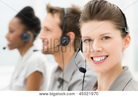 Portrait Of Beautiful Female Telephone Operator With Her Coworker
