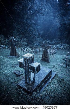 Spooky Halloween graveyard in fog in moonlight