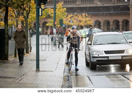 Young male cyclist in protective gear with backpack using walkie-talkie on street