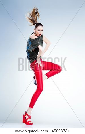 Sexy Model With Slim Body Dressed In Red Jumping And Screaming In The Studio Against Blueish Backgro