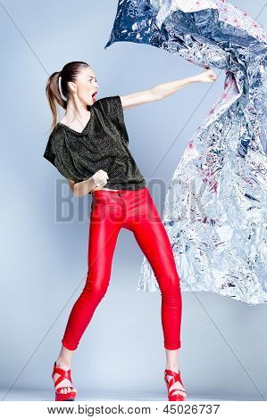 Sexy Model With Slim Body Dressed In Red Jumping In The Studio Against Blueish Background