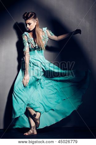 Beautiful Woman In Green Dress Posing Dramatic Indoors Against Grunge Background