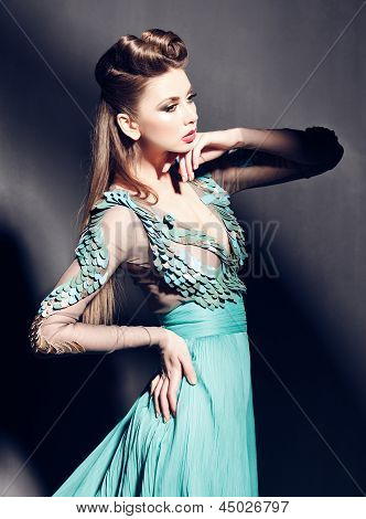 Beautiful Woman Portrait In Green Dress Posing Dramatic Indoors Against Grunge Background