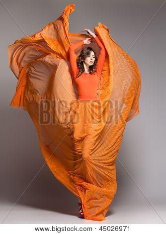 Beautiful Woman In Long Orange Dress Posing Dynamic In The Studio