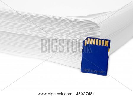 Sd Memory Card With A Stack Of Printer Paper. Hardcopy Backup Or Go Paperless Idea.