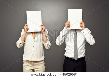 man and woman hiding their faces behind white paper