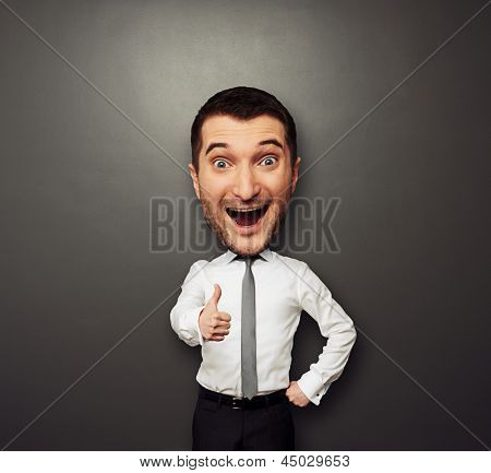 happy businessman with big head showing thumbs up. funny picture over dark background