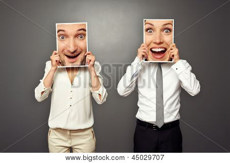 man holding frame with female happy face, woman holding frame with male happy face