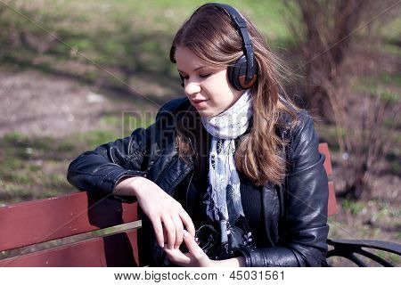 girl on a park bench drinking a glass of red wine