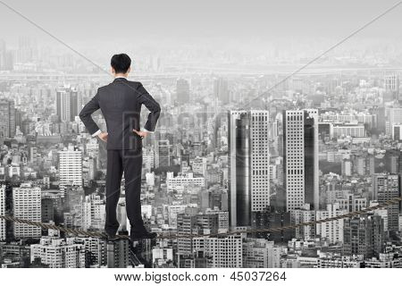 Chinese business man stand on rope. Photo manipulation  about risk, adventure, future or dream etc.