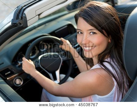 Happy casual woman driving a convertible car