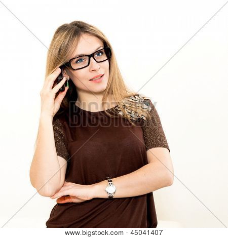 smiling woman in glasses talks by mobile phone on white background