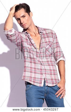 casual young man grooming his hair and holding a thumb in his pocket while looking at the camera. isolated on white background