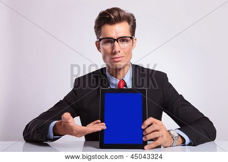 young business man sitting at the desk and presenting his tablet while looking at the camera