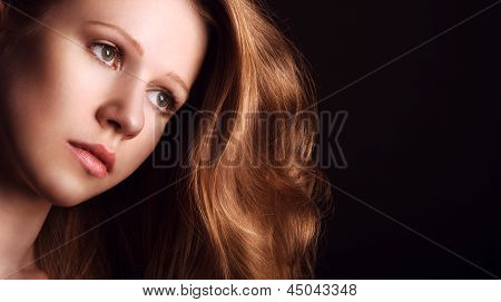 Sad, Melancholy Girl With Long Red Hair On A Dark Background