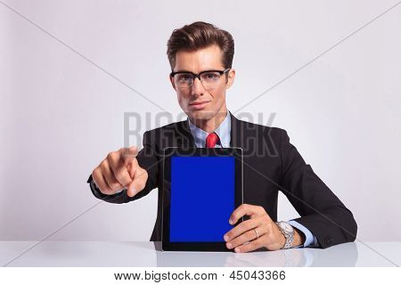 young business man sitting at the desk and presenting his tablet while pointing at the camera, on gray background