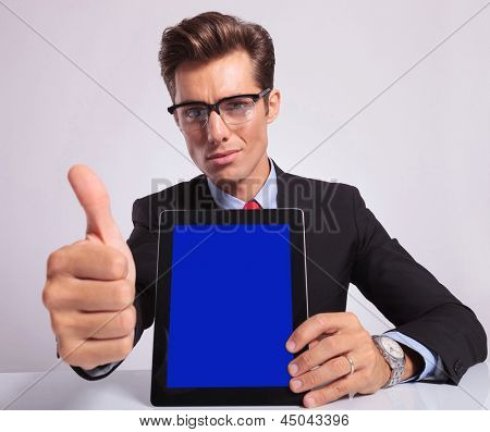 young business man presenting his tablet and showing thumbs up sign at the desk while looking at the camera, on a gray background