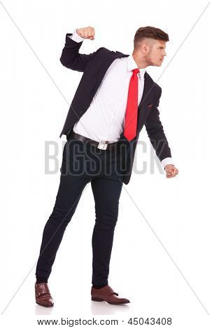 side view of a young business man threatening to punch someone. isolated on white background