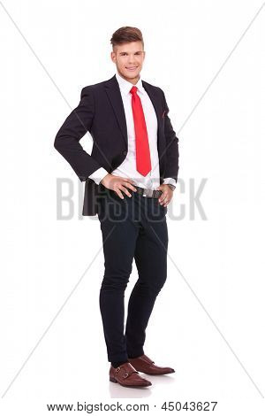 full length picture of a young business man standing with his hands on his waist and smiling to the camera. isolated on white background