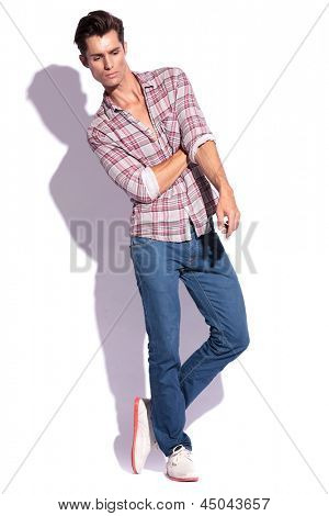young casual man poses with legs crossed and a hand beneath the other, looking down, away from the camera