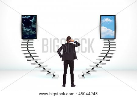 back of an undecided young business man standing with his hand on his head and thinking what to do