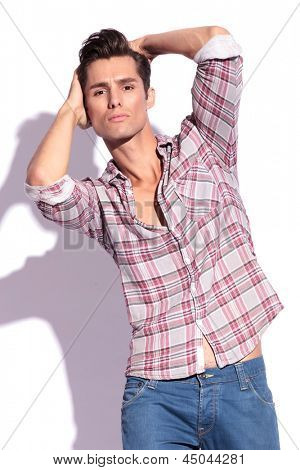 cutout picture of a casual young man posing with his hands behind his head and looking at the camera. isolated on white background