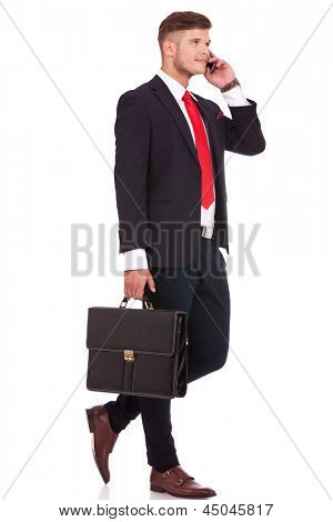 full length picture of a young business man walking with his briefcase and talking on the phone while looking away from the camera. isolated on white background