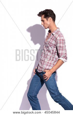 side view of casual young man with his thumbs in his pockets looking away from the camera. isolated on white background