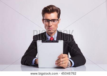 homem de negócios jovem sentado no balcão e trabalhando em seu tablet com um olhar sério sobre seu rosto