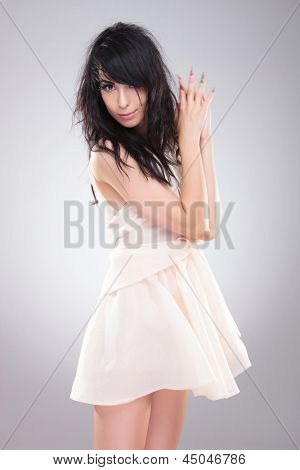 sexy young fashion woman standing with her hands together and with her hair roughed up. on gray background