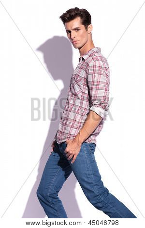 side view of casual young man stepping and looking at the camera with his thumbs in his pockets. isolated on white background