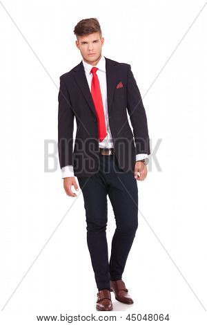full length picture of a young business man walking towards the camera with a serious look on his face. isolated on white background