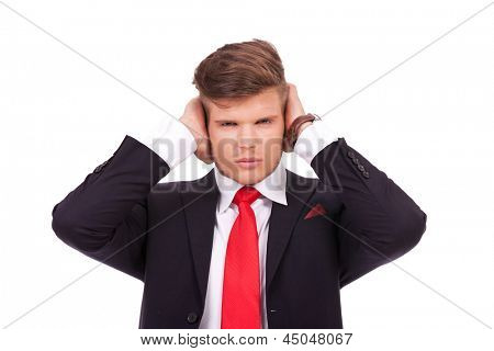 young business man covering his ears with his hands while looking at the camera. hear no evil. isolated on white background