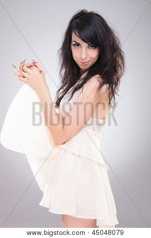 side view of a sexy young fashion woman holding her skirt up in front of her and smiling to the camera. on gray background