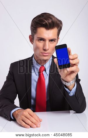 young business man sitting on the desk and showing you his phone, on a gray background