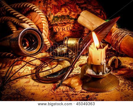 Vintage compass, magnifying glass, quill pen, spyglass lie on an old ancient map with a lit candle. Vintage still life.