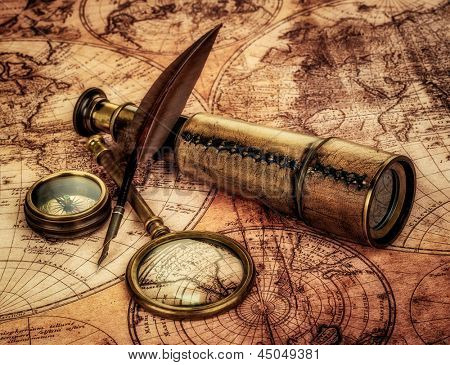 Vintage magnifying glass, compass, goose quill pen and spyglass lying on an old map.