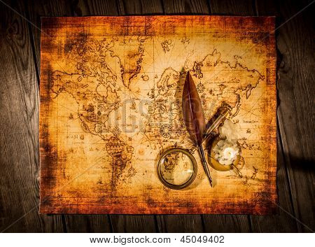 Vintage quill pen and magnifying glass lie on an old ancient map with a lit candle