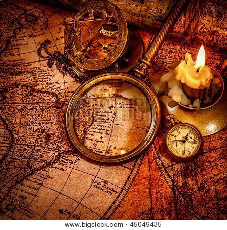 Vintage magnifying glass, pocket watch, compass, spyglass lie on an old ancient map with a lit candle