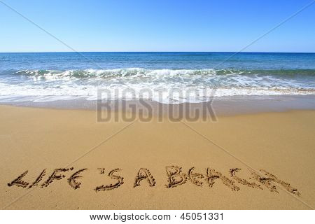 ?Life is a beach? written on golden sandy beach