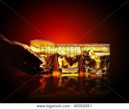 Three glasses of whiskey with ice cubes