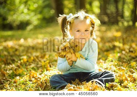 Cute little girl in autumn park holding bunch of yellow leaves
