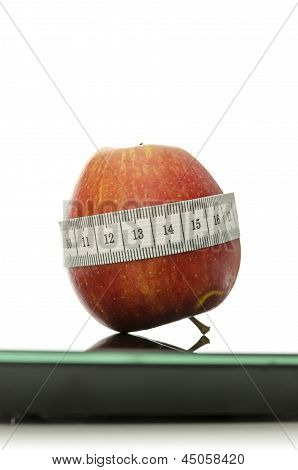Apple Wrapped With Measuring Tape On A Scale