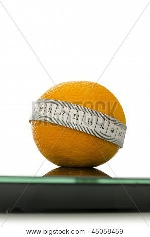 Closeup Of Orange On A Scale Wrapped With Measuring Tape